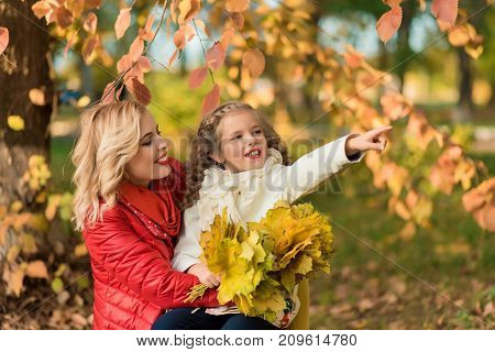Mother with daughter having fun at autumn time. Woman and young girl playing in the park smiling, hugging. happy family concept.