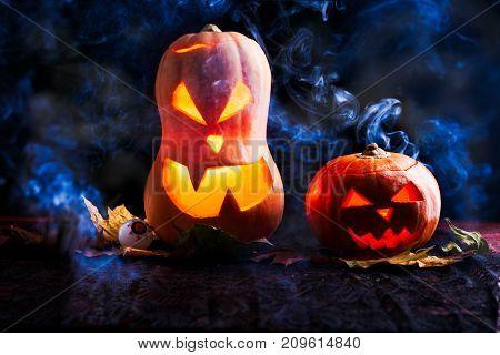 Image of two halloween pumpkins with eyeballs on black background with smoke