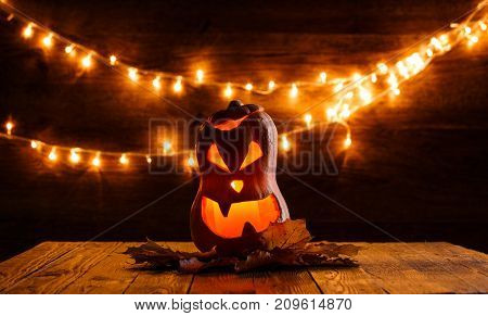 Photo of halloween pumpkin cut in shape of face on background with burning yellow lights