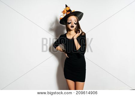 Happy Halloween Sexy Witch with a black hat and black patches under the eyes. Beautiful young woman in witches hat and costume laughing Isolated on white background