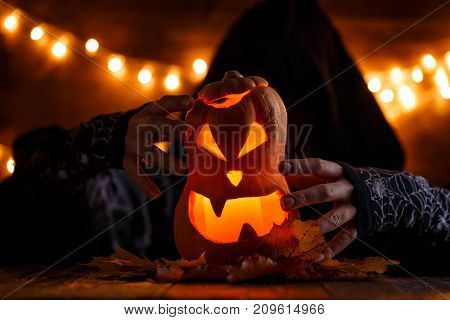 Photo of halloween pumpkin cut in shape of face with witch on background with burning yellow lights