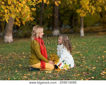 Young woman with child girl having fun outdoor. Beautiful family resting in the park. Sty family.