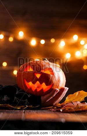 Picture of halloween background with pumpkin and witch hand on wooden table against grunge bokeh lights background