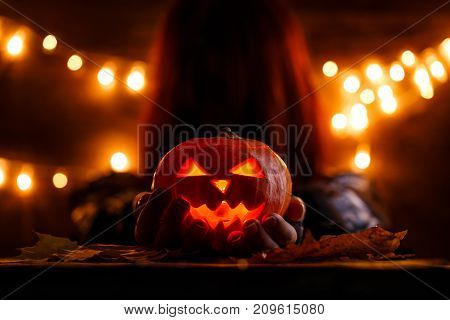 Photo of witch with long hair holding halloween pumpkin in background with burning garlands