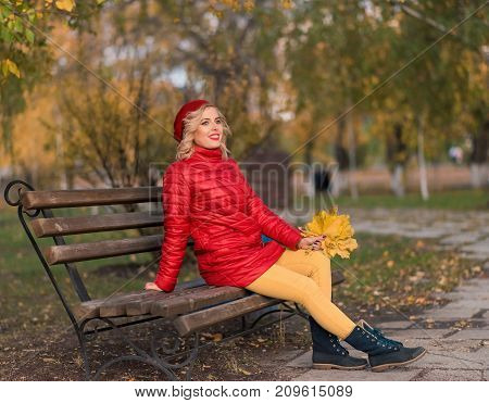 Portrait of smiling girl with leaves in her hands in autumn city park. Beautiful woman in red barret in the park. Autumn portrait.