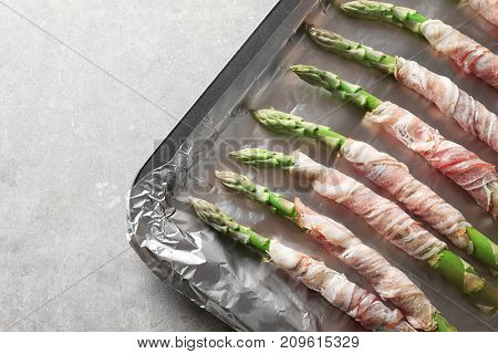 Plate with bacon wrapped asparagus on light background