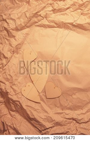Wooden hearts on crumpled kraft paper