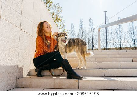 the lovely red-haired girl sat down on the steps and stroked her dog. walk with a dog in the park. Autumn warm day.