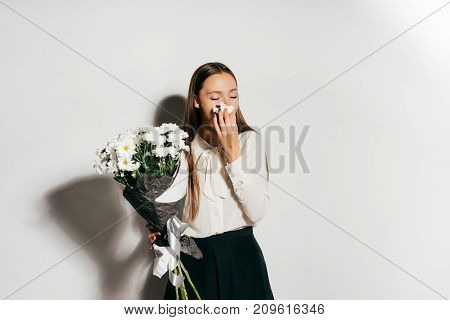 a beautiful young girl sneezes because she is allergic to the flowers she keeps in her hands
