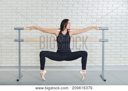 Beautiful ballet dancer practicing near barre at ballet studio, Ballerina full length portrait