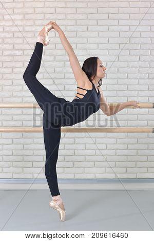 Ballerina stretches herself near barre at ballet studio, beautiful women in black bodysuit practicing ballet