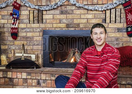 Teen Boy Smiling Sitting In Front Of Cozy Fireplace Decorated For Christmas