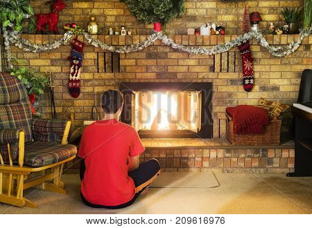 Teen Boy Sitting In Front Of Roaring Fire In Brick Fireplace Decorated For Christmas