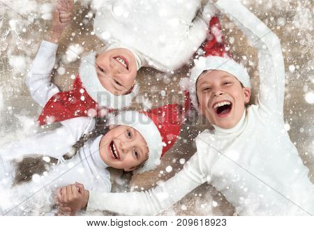 happy child hold hands and lying on wooden background, dressed in christmas Santa hat and having fun, winter holiday concept, snow decoration