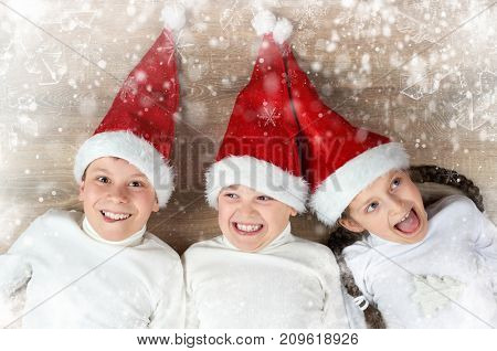 happy child lying together in a row on wooden background, dressed in christmas Santa hat and having fun, winter holiday concept, snow decoration