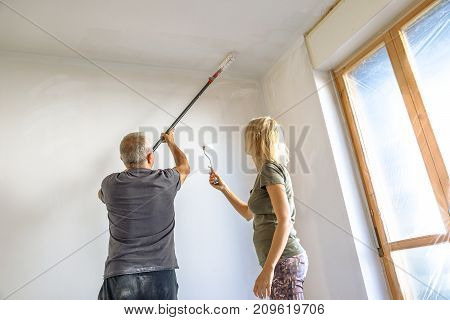 Caucasian housewife helping her whitewasher man at work painting a blank ceiling, with paint brush roller in empty white room for renovation.