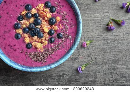 Bowl with acai smoothie, berries and muesli on grey background