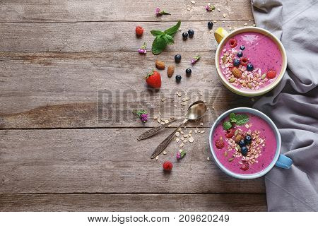 Cups with acai smoothie and berries on wooden background