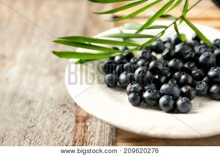 Plate with fresh acai berries on wooden table