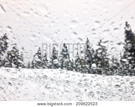 An abstract shot of snow melted droplets on glass looking into a winter wonderland scene.