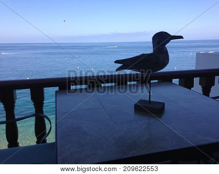 Silhouette of a sandpiper statue rests on the balcony of a ocean front house.