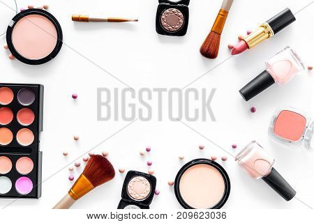 visagiste work table with decorative cosmetics of beige and nude tones set on white background top view mockup