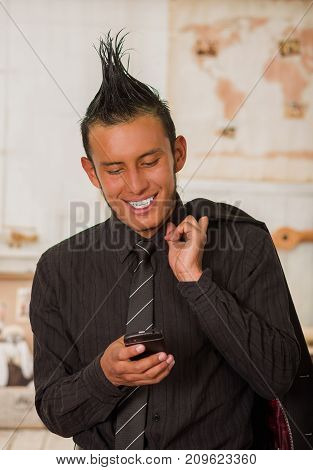 Close up of happy office punk worker wearing a suit with a crest, holding with one hand his jacket in the shoulder and using his cellphone in the office in a blurred background.