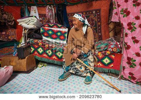 BAYAN-OLGII, MONGOLIA - SEP 28, 2017: Old woman from Kazakh family of hunters who hunt with golden eagles inside their the mongolian Yurts. In Bayan-Olgii Province is populated to 88,7% by Kazakhs.
