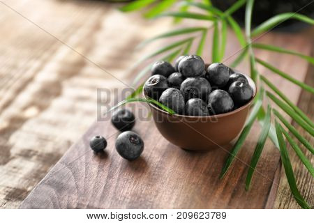 Bowl with fresh acai berries on wooden table, closeup