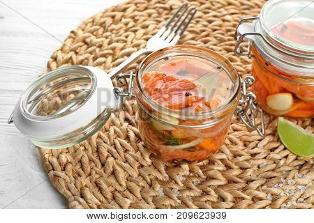 Jar with delicious marinated salmon on wicker mat