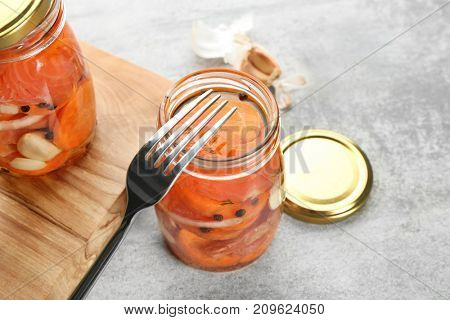 Jars with delicious marinated salmon on table