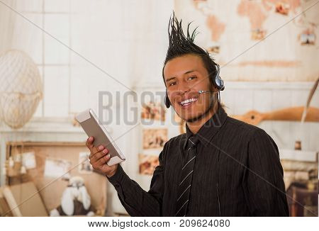 Close up of office punk man, wearing a suit with a crest, with headphones in his head and using his tablet in the office in a blurred background.