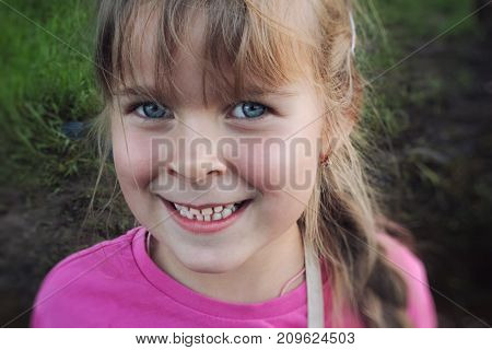 Happy smiling baby little girl of european and caucasian appearance on a background of green grass