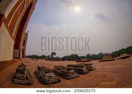 DELHI, INDIA - SEPTEMBER 19, 2017: Unidentified people walking in front of Humayun s Tomb, with the sun shinning through the clouds in Delhi, India. UNESCO World Heritage Site, it is the tomb of the Mughal Emperor Humayun, fish eye effect.