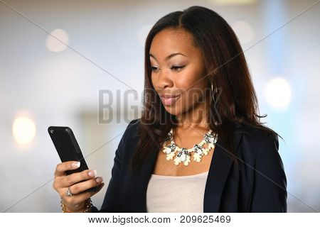 African American Businesswoman using cellphone inside building