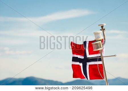 Norwegian flag on yacht ship mast sunny day blue sky background