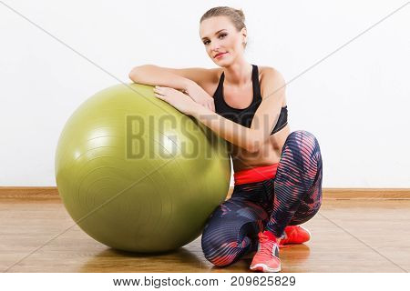 Cute Girl Sitting With Fitball At Gym