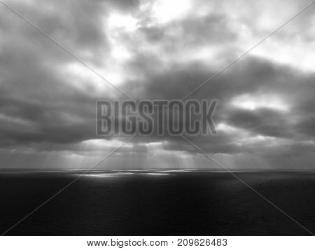 Dramatic black and white sky over the sea with beams of light shining down. Showing the horizon with space for text.