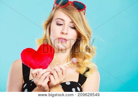Woman blonde lovely girl wearing dotted dress holding red heart love symbol and lollipop candy. Valentines day happiness sweet food concept