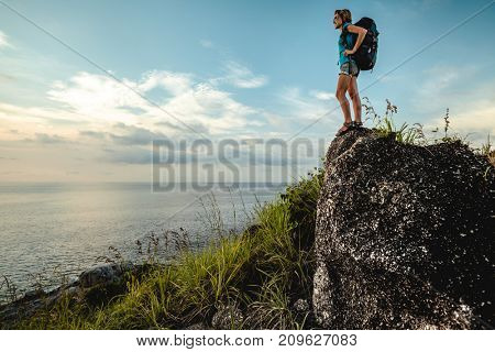 Lady hiker with backpack standing on the stone and enjoying sea view