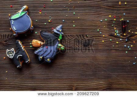 Cook halloween gingerbread cookies in shape of whitch, cat. wooden background top view copyspace.