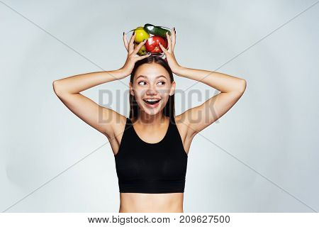 happy thin girl holding a plate with vegetables on her head and looking away.
