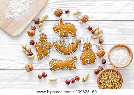 Healthy food for sportsman. Cookies in shape of yoga asanas near nuts on white wooden desk background top view copyspace