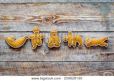 Gingerbread cookies in shape of yoga asanas on wooden background top view.