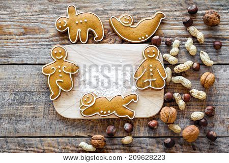 Healthy food for sportsman. Cookies in shape of yoga asanas near nuts on wooden desk background top view