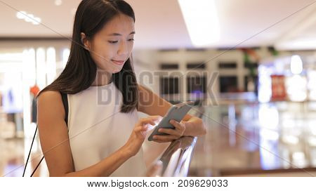 Woman using mobile phone in shopping center