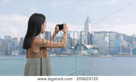 Woman taking photo on cellphone in Hong Kong