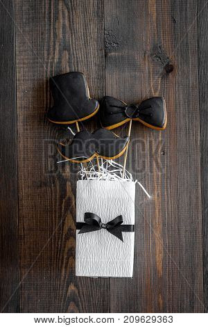 Happy father's day morning with black tie, mustache and hat cookies on sticks, gift box for celebrate on wooden background top view mock up