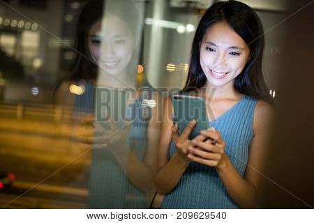 Woman working on mobile phone in the city at night