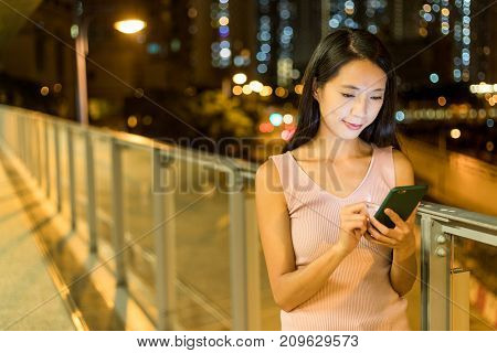 Asian woman watching on cellphone at night